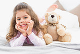 Girl lying on bed with teddy bear