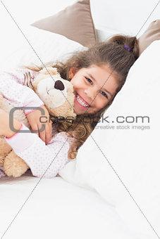 Little girl cuddling teddy bear