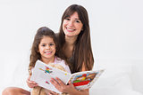 Happy mother and daughter with storybook