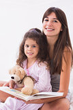 Mother and daughter reading together with teddy bear