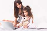 Happy mother and daughter using the laptop