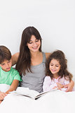 Mother and children reading book together