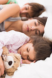 Mother and children cuddled up in bed