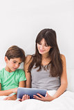 Happy mother using tablet pc with son
