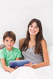 Smiling son and mother using tablet