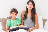 Happy mother and son reading book