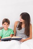 Smiling mother and son reading in bed
