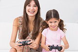 Happy mother and daughter playing video games