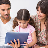 Parents watching daughter using tablet pc