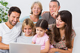Smiling family watching something on laptop