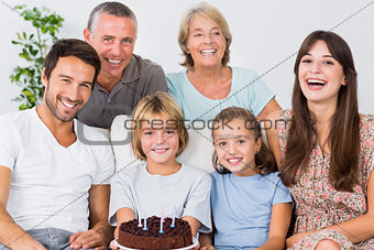 Smiling family with birthday cake