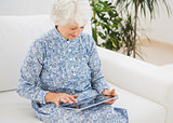 Elderly smiling woman using a digital tablet