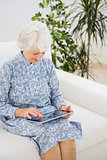 Elderly cheerful woman using a digital tablet