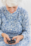 Elderly smiling woman using a smartphone