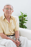 Elderly man sitting on the sofa
