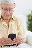 Focused elderly man using his smartphone