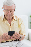 Calm elderly man using his smartphone