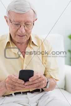 Calm elderly man using his smartphone