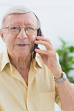 Smiling elderly man calling someone