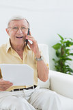 Elderly smiling man reading papers on the phone