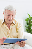 Elderly focused man using a digital tablet