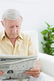 Elderly focused man reading newspapers