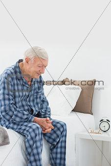 Calm elderly man sitting on the bed