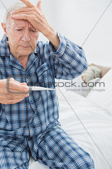 Old man taking his temperature