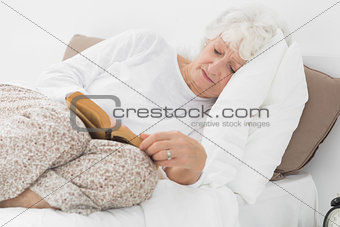 Old woman lying on the bed and reading