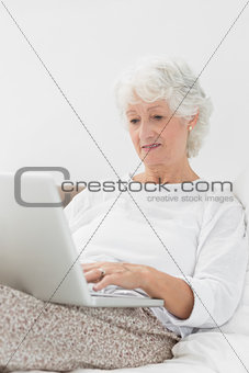 Aged woman typing on her laptop