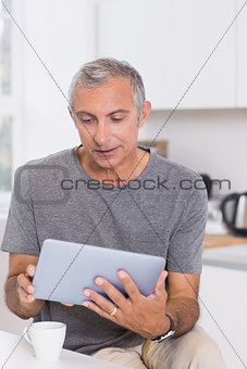 Focused man using his digital tablet