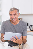 Smiling man using his digital tablet