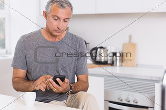 Focused man touching his smartphone