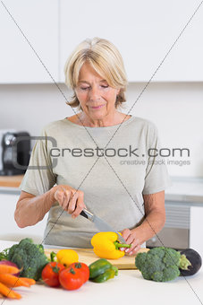Cheerful woman cutting a yellow pepper
