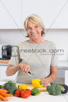 Mature woman cutting a yellow pepper