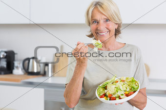 Smiling woman eating salad