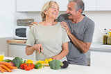 Smiling couple cutting vegetables together