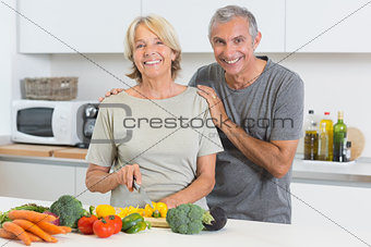 Happy couple cutting vegetables together