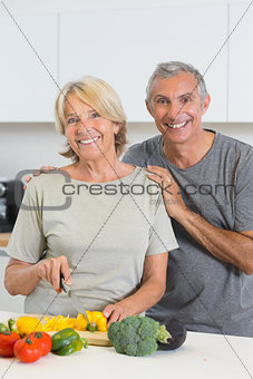 Cheerful couple cutting vegetables together
