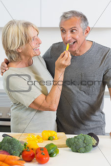 Smiling husband tasting a slice of yellow pepper