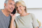 Cheerful mature couple listening a call together