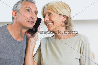 Happy mature couple listening a call together