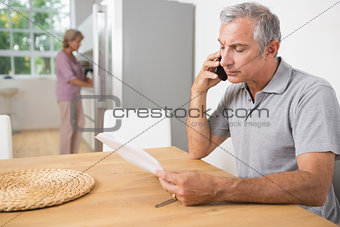 Man calling and reading a sheet of paper