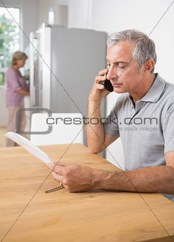 Mature man calling with a sheet of paper