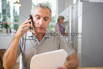 Focused man calling with a sheet of paper
