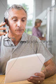 Focused mature man calling with a sheet of paper