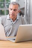 Serious mature man using his laptop