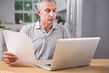 Calm mature man using his laptop