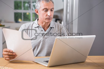 Calm mature man using his laptop