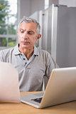 Thoughtful man using his laptop